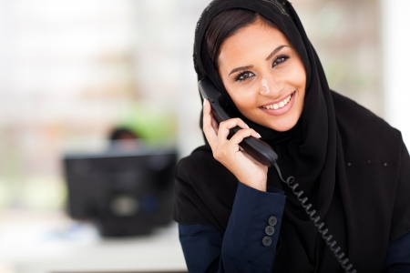 middle eastern ethnicity: young happy Muslim businesswoman talking on landline phone