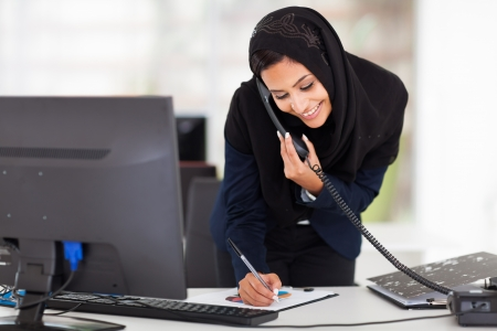 hijab: happy young middle eastern businesswoman working in office Stock Photo