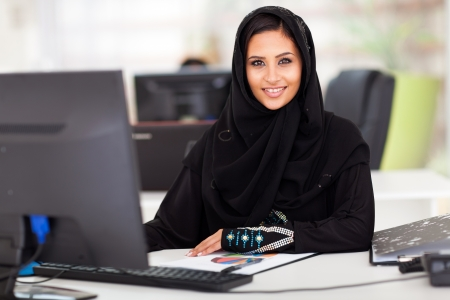 attractive modern Arabian businesswoman in traditional clothing working in office photo