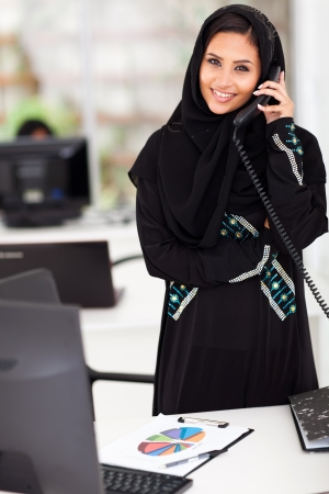 young Muslim businesswoman talking on office phone photo