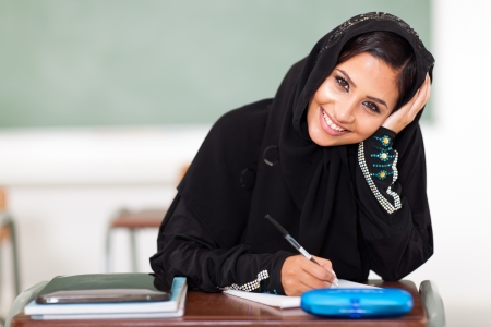 middle eastern ethnicity: happy female middle eastern high school student sitting in classroom