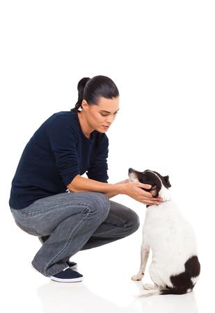 mujer con perro: hermosa mujer joven jugando con su perro en el fondo blanco Foto de archivo