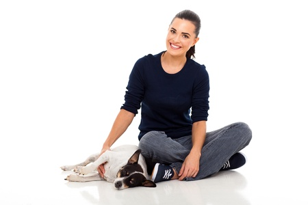 smiling young woman sitting on floor with her dog next wo her isolated on white photo