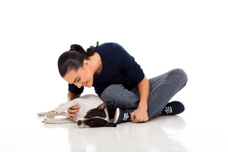 casual woman sitting on floor and playing with her dog photo