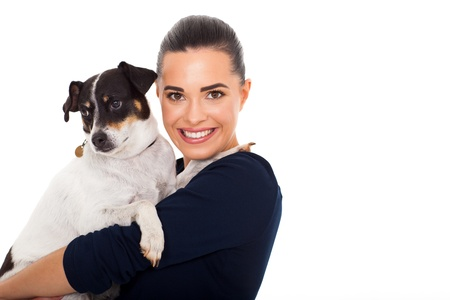 happy young woman holding her pet dog on white background photo