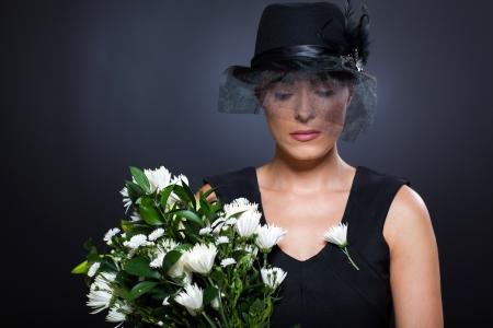 triest jonge weduwe met zwarte rouw hoed en bloemen Stockfoto