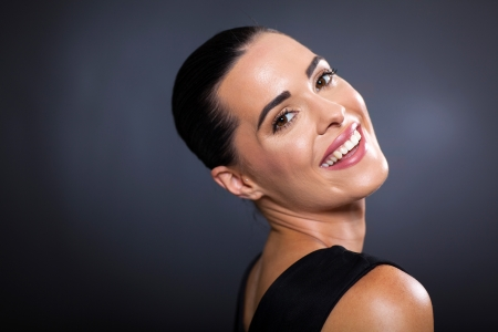 woman black background: pretty woman smiling and looking back on black background