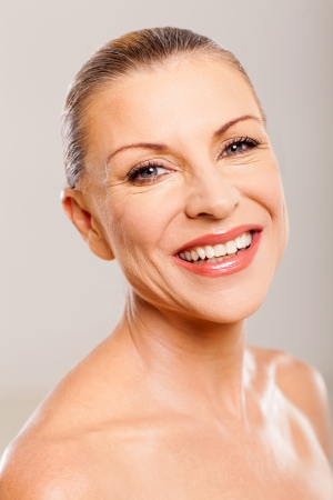pretty mature woman smiling against plain background Stock Photo - 18661300