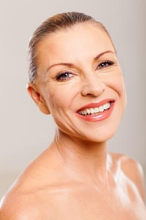 pretty mature woman smiling against plain background
