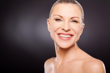 elegancy: gorgeous mid age woman smiling against black background