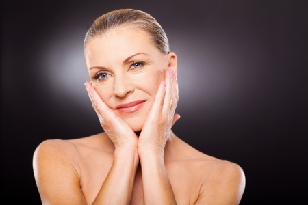 elegancy: portrait of attractive well-groomed mid age woman touching face Stock Photo