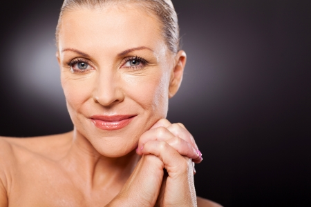 mature woman: portrait of beautiful mid aged woman close up over black background