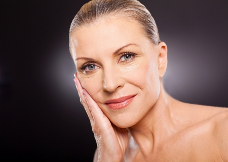 beautiful skin: potrait of elegant mature woman over black background