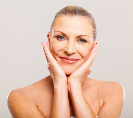 mature adults: portrait of pretty senior woman with hands on her face Stock Photo