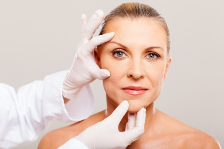 plastic glove: surgeon doing skin check on mid age woman before plastic surgery Stock Photo