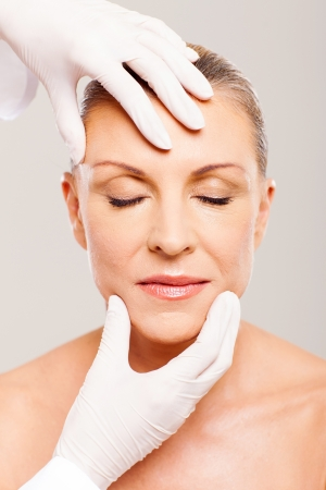 middle age women: plastic surgeon checking middle aged womans face after operation