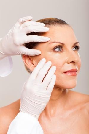 dermatologo: medico facendo controllo della pelle in et� met� volto di donna su sfondo bianco