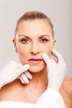doctor checking middle aged woman lips before plastic surgery Stock Photo - 18661270