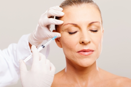 beautician giving face lifting injection on mature woman Stock Photo - 18661252