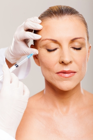 cosmetic surgeon injecting mid age woman face photo
