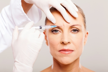 mature woman face: cosmetic surgeon giving face lifting injection to mature woman