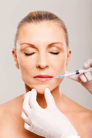 pretty mature woman receiving cosmetic injection on her lips photo