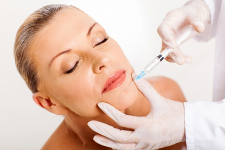 chin: pretty middle aged woman receiving cosmetic injection on her chin Stock Photo