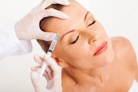 beauty care: doctor giving face lifting injection on mature woman