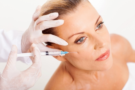 elegancy: doctor giving mid age woman face lifting injection closeup