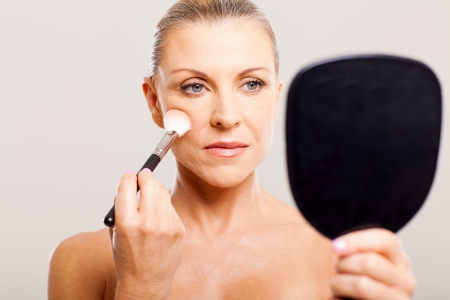 middle aged woman applying makeup on her face photo