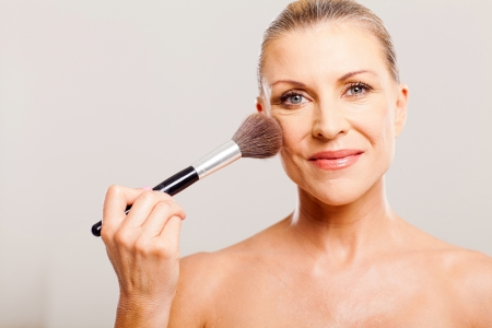 portrait of beautiful mature woman applying make up photo