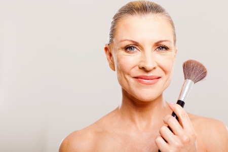 makeover: beautiful senior woman after applying make up holding a brush Stock Photo