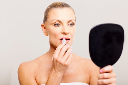 lip stick: portrait of beautiful middle aged woman putting lip stick