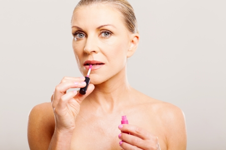 portrait of older woman putting lip gloss close up photo