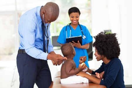 happy patient: male african pediatric doctor examining a child in office