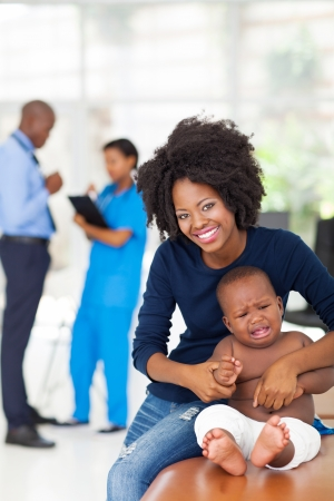 sick baby: african mother and her sick baby boy waiting for checkup in doctor Stock Photo