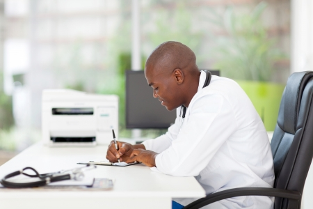 male african medical doctor writing reports in his office photo