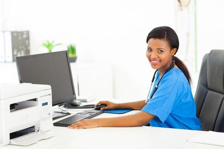 uniformes de oficina: afro americano bastante femenina médico sentado en la oficina moderna