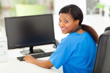 nurse uniform: retrato de la atractiva enfermera africano femenino en la oficina moderna