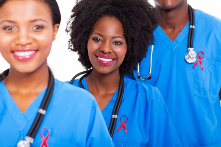 hiv ribbon: group of happy african healthcare workers with red ribbon for AIDS awareness Stock Photo
