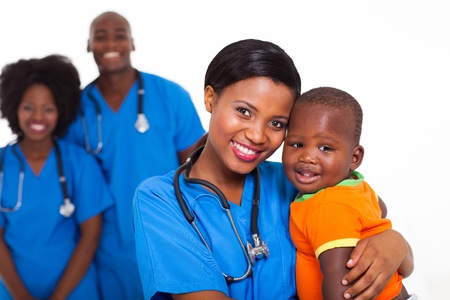 African children: beautiful black pediatrician and baby boy with co-workers on background
