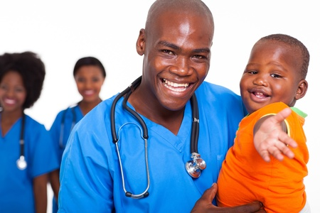 nurse and patient: african male pediatric doctor playing with baby boy, and colleagues on background