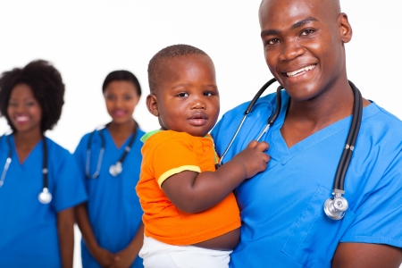 portrait of good looking african american male pediatric doctor with little boy and female nurses on background photo