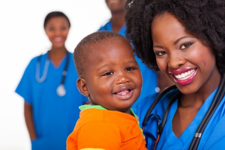 pediatric nurse: happy young african nurse carrying baby boy with colleagues on background Stock Photo