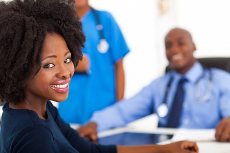 doctor visit: pretty african woman visiting her doctor in office Stock Photo