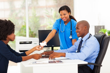 modern doctor: caring african nurse handover tissue to sick patient in doctors office