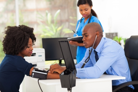 african medical doctor monitoring patient's blond pressure in his office photo