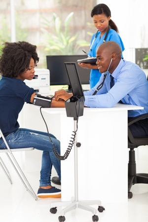 african medical doctor measuring patients blood pressure in office photo
