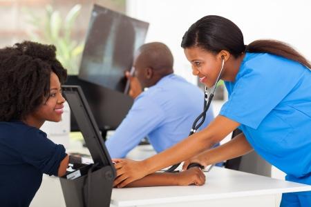 personal medico: feliz paciente africano enfermera médico medir la presión arterial en el consultorio médico