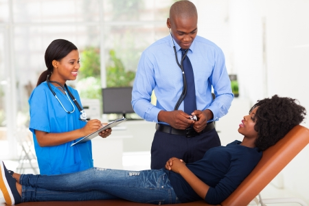 female African patient lying on doctors examining couch and complaining to doctor about her sickness photo